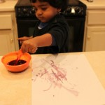 Arjun painting with feather and bluberry paint